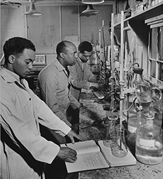 Paul L. Imes, Samuel C. Watkins, and George W. Richardson were employed in 1942 as laboratory technicians by TVA at its plant at Muscle Shoals. They were doing high-grade sub-professional work and were in training for professional positions. Photograph by Alfred T. Palmer